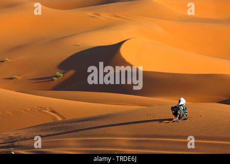 Berber sitting in desert sand, Morocco, Merzouga, Erg Chebbi - Stock Photo