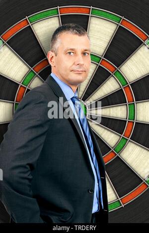 Halbportraet eines Geschaeftsmanns im grauen Anzug, stehend vor einem uebergrossem Dartscheibe | Half length portrait of a Businessman in a grey suit - Stock Photo