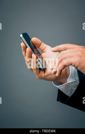 Close-up view of a hand with a black suit holding a smartphone against grey background - Stock Photo