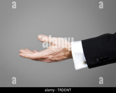 Close-up view of empty open hand in a black suit against grey background - Stock Photo