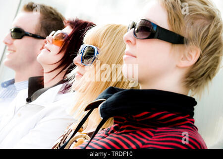 Group portrait/side view of 4 young persons wearing sunglasses sitting - Stock Photo