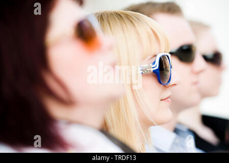 Group portrait/close up of 4 young persons wearing sunglasses sitting - Stock Photo