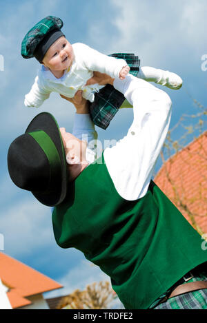 Portrait of a young man dressed in traditional costume holding up a baby, Germany, Bavaria