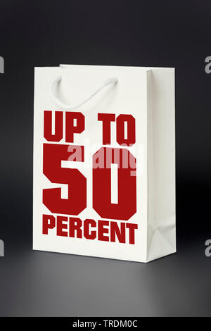 3D computer graphic, shopping bag in white color lettering UP TO 50 PERCENT - Stock Photo