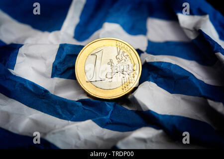 euro coin on a Greek flag, Greece - Stock Photo