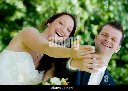 Bridal couple showing off their wedding rings after the ceremony and smiling - Stock Photo