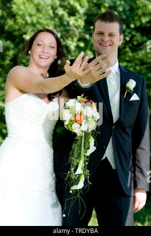 Bridal couple showing off their wedding rings after the ceremony - Stock Photo