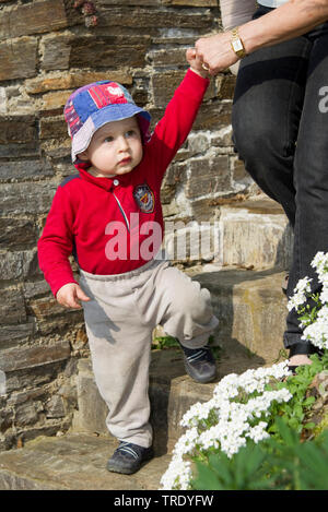 Portrait of a young boy walking down stairs with one hand hold by an adult - Stock Photo