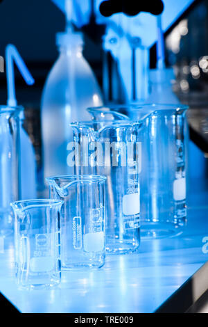 Serveral different flasks and beaker glasses on a laboratory bench illuminated in blue light - Stock Photo