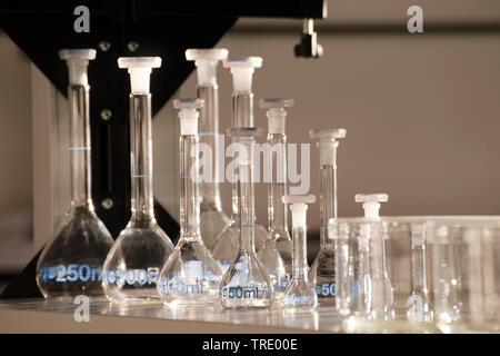 Serveral different conical flasks and beaker glasses on a laboratory bench - Stock Photo