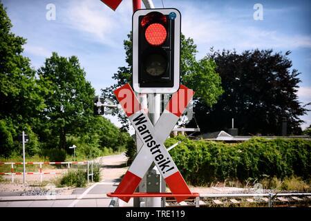 Closed railway crossing lettering WARNSTREIK (warning strike) symbolizing rail strike, Germany - Stock Photo