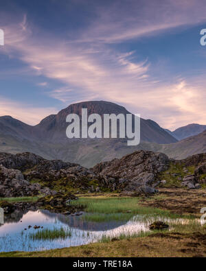 The warm morning light on the lakeland mountain of Great Gable reflecting in Innominate Tarn - Stock Photo