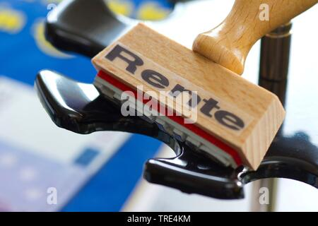 stamp on a rubber-stamp holder lettering Rente, pension, Germany - Stock Photo