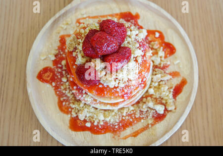 Pancakes strawberry fruit and sauce on wooden background - Stock Photo
