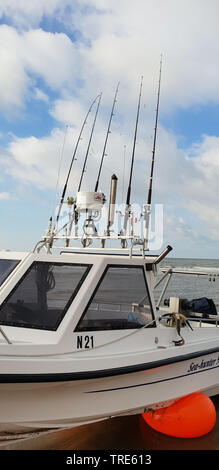 boat with a lot of fishing rods on the beach of the North Sea, Netherlands - Stock Photo