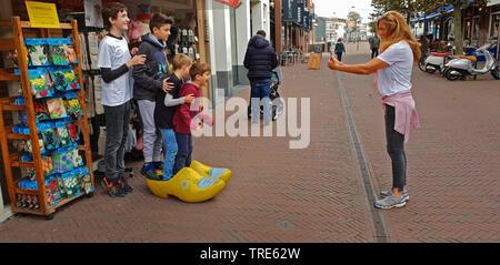 four brothers posing in front of a souvenir photo in clogs, Netherlands, Noordwijk aan Zee - Stock Photo