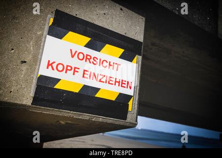 warning sign Kopf einziehen!, kee your head down, at the sea bridge in Timmendorfer Strand, Germany, Schleswig-Holstein - Stock Photo