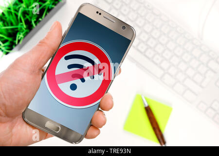 Hand haelt Smartphone mit durchgestrichenem WLAN-Symbol, Symbolfoto Funkloch, Deutschland | hand with smartphone and the sign dead zone, Germany | BLW - Stock Photo
