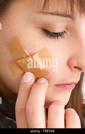 Young women with closed eyes, touching a plaster on her cheek - Stock Photo