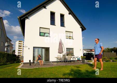 Couple in der garden of a newly built single family house, man standing on the loan - Stock Photo