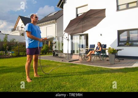 Couple in der garden of a newly built single family house, man watering the garden - Stock Photo
