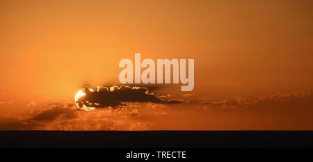 Simply orange sunset behind clouds - Stock Photo