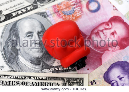 US and chinese bills next to a red boxing glove - trade conflict - Stock Photo