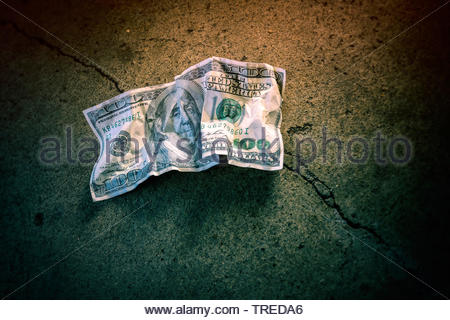 Crumpled 100 Dollar note lying on the ground - increasing national deficit in the US - Stock Photo