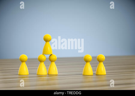 Number of yellow pawns building a pyramid - teamwork - Stock Photo