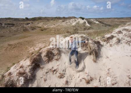 jumping kid in the dunes on Texel, Netherlands, Texel, De Slufter - Stock Photo
