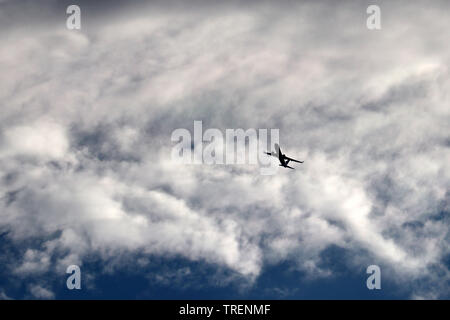 Airplane flying in the sky on background of clouds. Silhouette of a commercial plane during the turn - Stock Photo