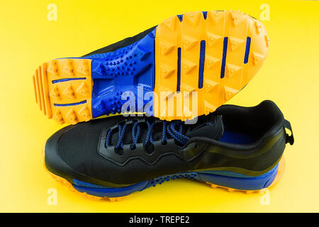 black sneaker with orange insert, mesh fabric, on a yellow background, running and fitness sneakers on yellow background - Stock Photo