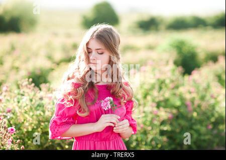 beautiful blonde teen girl 14 16 year old wearing pink dress holding rose flower outdoors summer portrait