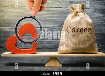 Bag with money with the word Career and red wooden heart on the scales. Money versus love concept. Passion versus profit. Family or career choice. Fam - Stock Photo