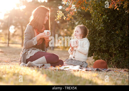 Mother drinking tea with kid daughter 4-5 year old  sitting in sun light in park. Wearing autumn knitted clothes. Looking at each other. Motherhood. C - Stock Photo