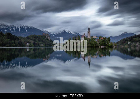 Dramatic sky with moving clouds over Assumtion of Mary church on island at Lake Bled, Slovenia. Long time exposure view of church and castle Bled refl - Stock Photo