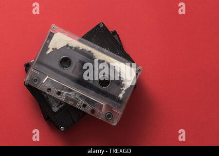 Audio cassette tape on red backgound, from above - Stock Photo