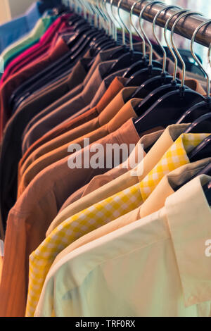 Vintage style image of male mens shirts on hangers in a shop display or wardrobe closet rail - Stock Photo