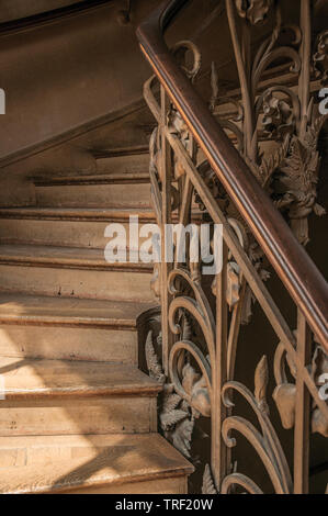 Close-up of wooden staircase on the sunlight and Nouveau style iron balustrade in Paris. One of the most impressive world's cultural center in France. - Stock Photo