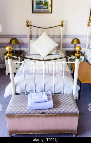 Old fashioned metal single bedstead in an bedroom decorated in Victorian style. - Stock Photo