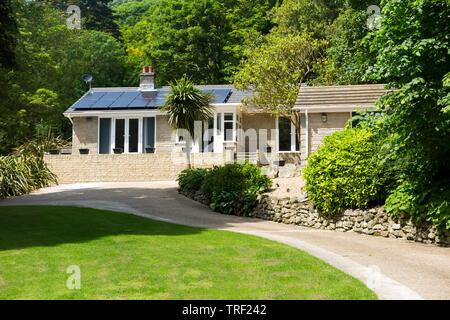 Bungalow house with solar panels on the roof near Ventnor on the Isle of Wight. Beautiful residential property with drive and large generous garden on a sunny day with blue skies. UK. (99) - Stock Photo