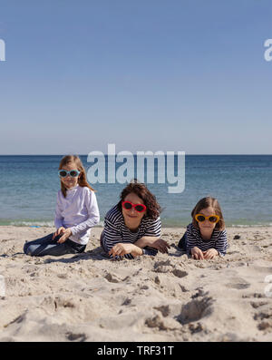 Walk moms with children on the beach. Sisters (8 and 7 years old) and younger brother (3 years old) are playing at sea. Selective focus. - Stock Photo