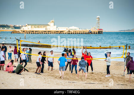 Volleyball on Bournemouth beach with the Pier to the rear. Dorset. England, UK. - Stock Photo