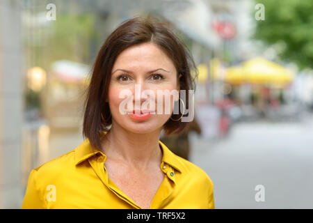 Attractive stylish middle aged woman standing in a quiet street in town looking thoughtfully at the camera in a close up portrait - Stock Photo