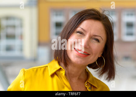 Attractive middle aged brunette woman with a lovely big warm friendly smile standing in a quiet street in the city, close up head and shoulders portra - Stock Photo