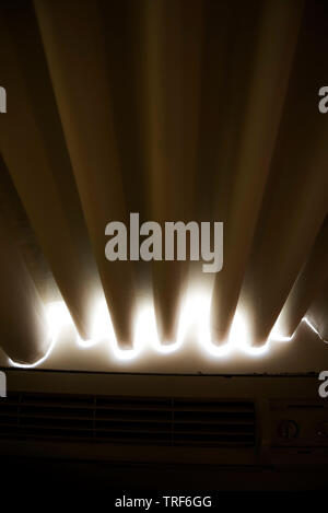 Sunlight coming through the bottom of a motel room curtain. - Stock Photo