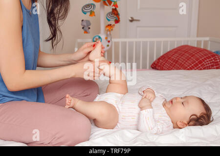 Portrait of cute adorable mixed race Asian mother with newborn baby doing massage and physical exercises. Early development and health care lifestyle