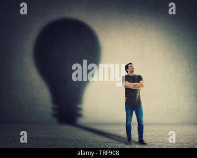 Confident man, keeps arms crossed, casting a lightbulb shape shadow on the wall. Ambition and business idea concept. Motivation and inner power symbol - Stock Photo
