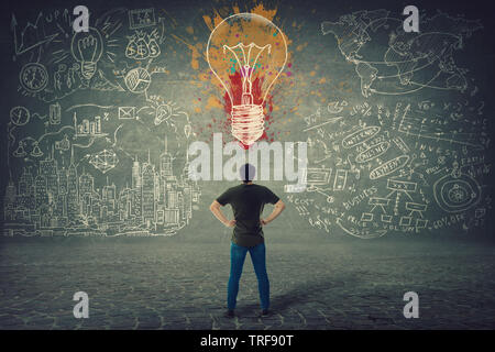 Rear view of confident young man, hands on hips, stands in front of a wall with drawn colorful light bulb and business sketches. Uniqueness of the ide