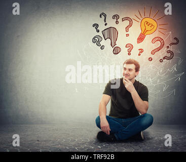 Pensive man sitting on the floor holding hand under chin has many questions as interrogation marks above head and one bright idea as lightbulb glowing - Stock Photo